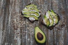 Avocadotoost met zaden op houten uitstekende achtergrond Plakken van avocado op het volkorenbrood met zonnebloem en lijnzaad royalty-vrije stock afbeeldingen