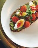 Avocadotoost op plaat met zacht-gekookt ei, kersentomaten, koriander Royalty-vrije Stock Foto's