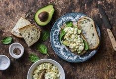 Avocat, épinards, salade d'oeufs sur le sandwich à pain grillé Petit déjeuner sain de nourriture, casse-croûte sur le fond en boi Images libres de droits