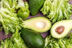 Avocat, chaux, salade sur un fond brun Image stock
