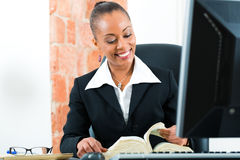 Avocat dans le bureau avec le livre et l'ordinateur de loi Images stock