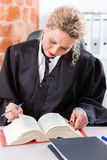 Avocat dans le livre de loi de lecture de bureau Images stock
