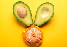 Avocat et mandarine sur le fond jaune Photographie stock libre de droits