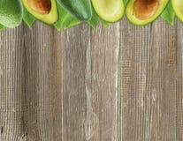 Avocat frais avec des feuilles sur le fond en bois Photo libre de droits
