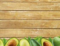 Avocat frais avec des feuilles sur le fond en bois Photos stock