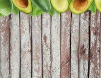 Avocat frais avec des feuilles sur le fond en bois Images stock