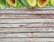 Avocat frais avec des feuilles sur le fond en bois Photo stock