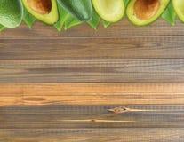 Avocat frais avec des feuilles sur le fond en bois Image libre de droits