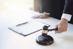 Avocat mûr travaillant à la salle d'audience avec le marteau de justice en main image libre de droits
