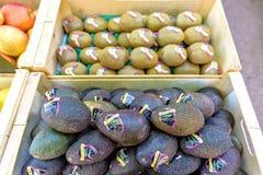 Avocat, pommes et kiwi dans des boîtes en bois à vendre Image stock