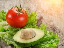 Avocat, tomates et salade sur le conseil en bois Images libres de droits
