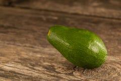 Avocat vert brillant sur le bois photos stock