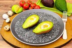 Avocats, cuits au four avec l'oeuf de caille, sel, poivre Images stock