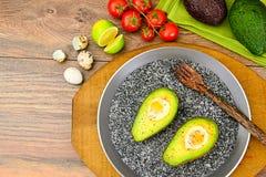 Avocats, cuits au four avec l'oeuf de caille, sel, poivre Image stock
