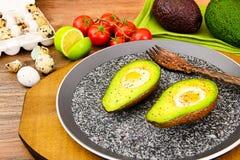 Avocats, cuits au four avec l'oeuf de caille, sel, poivre Photo stock