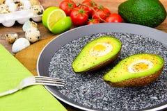 Avocats, cuits au four avec l'oeuf de caille, sel, poivre Photos libres de droits