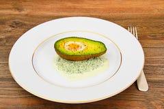 Avocats, cuits au four avec l'oeuf de caille, sel, poivre Photo libre de droits