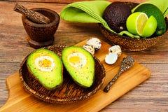 Avocats, cuits au four avec l'oeuf de caille, sel, poivre Photographie stock libre de droits