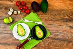 Avocats, cuits au four avec l'oeuf de caille, sel, poivre, citron Photo libre de droits