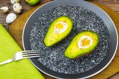 Avocats, cuits au four avec l'oeuf de caille, sel, poivre, citron Photographie stock libre de droits