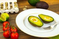 Avocats, cuits au four avec l'oeuf de caille, sel, poivre, citron Image libre de droits