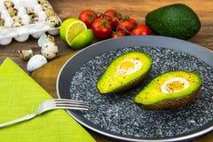 Avocats, cuits au four avec l'oeuf de caille, sel, poivre, citron Photos libres de droits