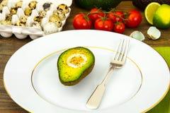 Avocats, cuits au four avec l'oeuf de caille, sel, poivre, citron Images libres de droits