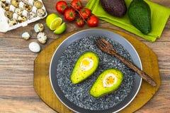 Avocats, cuits au four avec l'oeuf de caille, sel, poivre, citron Image stock