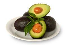 Avocats entiers et demi sains frais de hass avec des feuilles de basilic couvertes en jus de citron d'un plat blanc sur le fond b Image stock