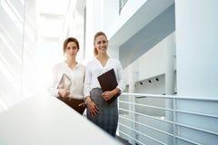 Avocats féminins élégants tenant le pavé tactile et le dossier tout en se tenant dans l'intérieur de bureau après la réunion réus Image libre de droits