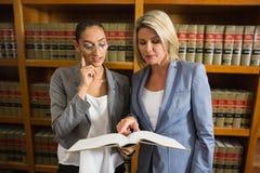 Avocats parlant à la bibliothèque juridique Photo stock