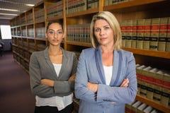 Avocats regardant l'appareil-photo à la bibliothèque juridique Image libre de droits