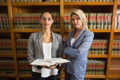 Avocats regardant l'appareil-photo à la bibliothèque juridique Image stock