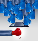 Avoid Competition. Business concept as a group of blue boxing gloves raining down on a red glove boxer protected by an umbrella as an icon of competitive Royalty Free Stock Image