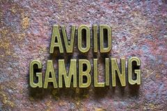 Avoid gambling. Phrase made from metallic letters over rusty metallic background royalty free stock photography
