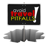 Avoid Travel Pitfalls Warning Sign Hole Trouble Problem. Avoid Travel Pitfalls words on a sign in a hole warning you to watch for problems in reservations and Royalty Free Stock Image