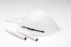 Avoiding cigarettes. Breathing mask with cigarettes on a graduated white background royalty free stock photo