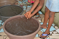 AVOIDING MICROBES THROUGH HAND WASHING. African children washing their hands with liquid soap which is a better way to prevent the spread of infections Stock Photos