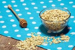 Avoine dispersée sur la table, versée dedans une cuvette et une cuillère pour le miel Photos libres de droits