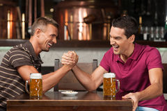 Avoir l'amusement à la barre. Deux amis buvant de la bière et ayant l'amusement Photos libres de droits