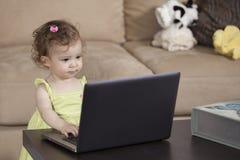 Avoir l'amusement avec l'ordinateur portable du papa Photographie stock libre de droits