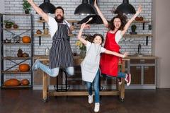 Avoir l'amusement dans la cuisine Le papa de maman de famille et les petits tabliers d'usage de fille sautent dans la cuisine Fam images stock