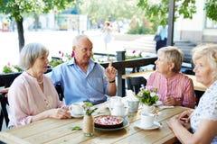 Avoir le petit entretien en café extérieur Image stock