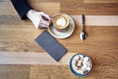 Avoir un latte de café ou un cappuccino dans un café, table en bois Photo libre de droits