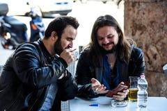Avoir une fumée avec de la bière vérifiant quelque chose sur l'Internet Image libre de droits
