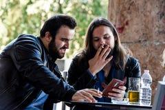 Avoir une fumée avec de la bière vérifiant quelque chose sur l'Internet Photos libres de droits