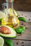 Avokado, limefrukt, olivolja och kryddor på den gamla träbakgrunden royaltyfria foton