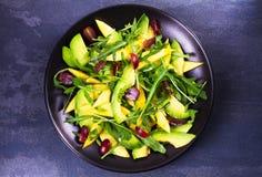 Avokado, mango, röd druva och arugulasallad på den svarta plattan Royaltyfri Fotografi