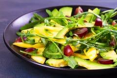 Avokado, mango, röd druva och arugulasallad på den svarta plattan Fotografering för Bildbyråer