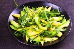 Avokado, mango, röd druva och arugulasallad på den svarta plattan Arkivfoton